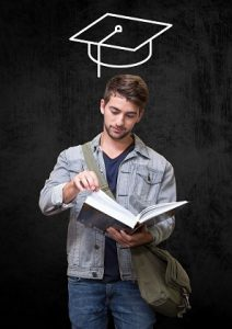 Teenage Student With Mortarboard Above Head Reading Book Against Black Background